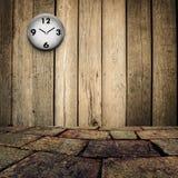 Alte Uhr auf grungy hölzerner Wand und Ziegelsteinboden Stockfotografie