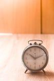 Alte Uhr auf hölzerner Tabelle Lizenzfreie Stockfotos