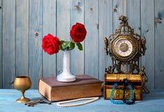 Alte Uhr, Bücher, Blumen und Schmuck Stockbilder