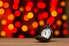 Alte Uhr der Nahaufnahmeweinlese im bokeh auf braunem hölzernem Hintergrund Stockfotos
