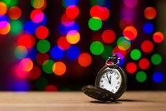 Alte Uhr der Nahaufnahmeweinlese im bokeh auf braunem hölzernem Hintergrund Stockfotografie