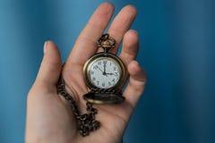 Alte Uhr der Weinlese auf einer Kette Hand, die eine Uhr auf einer Kette hält Lizenzfreies Stockbild