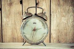 alte Uhr des Schmutzes im hölzernen Hintergrund Lizenzfreies Stockfoto