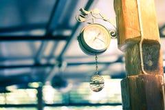 Alte Uhr, die an einem Pfosten am Abend hängt Lizenzfreie Stockbilder