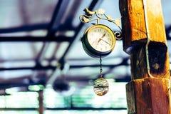 Alte Uhr, die an einem Pfosten am Abend hängt Lizenzfreie Stockfotos