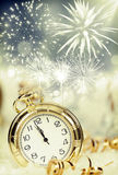 Alte Uhr mit Feuerwerken und Lichterkette Stockfotografie