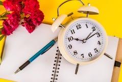 Alte Uhr, Rotrosenblume, Stift auf Notizbuch, Retro- Konzeptbild Stockfoto