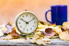 Alte Uhr und blaue Teeschale auf Herbstlaub auf Holztisch auf n Stockfotografie