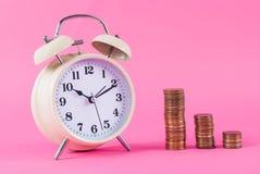 Alte Uhr und goldene Münzen auf rosa Hintergrund Lizenzfreie Stockbilder
