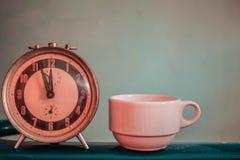 Alte Uhr und Kaffeetasse Stockfoto