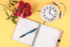 Alte Uhr- und Rotrosenblume und Notizbuch, Retro- Konzeptbild Lizenzfreie Stockbilder