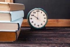 Alte Uhr und Stapel alte Bücher Stockbilder