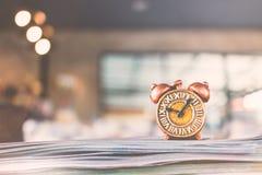 Alte Uhr und Stapel des Buches Stockfotografie