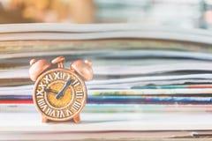 Alte Uhr und Stapel des Buches Stockbild