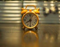 Alte Uhrorange auf dem Holztisch Lizenzfreies Stockfoto