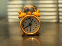 Alte Uhrorange auf dem Holztisch Lizenzfreies Stockbild