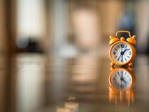 Alte Uhrorange auf dem Holztisch, Stockfoto