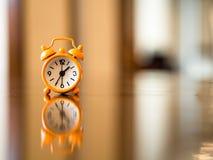 Alte Uhrorange auf dem Holztisch, Stockfotos