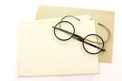 Alte Umschläge und ein Paar Gläser Stockbild