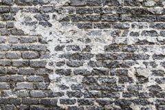 Alte und abgedroschene Backsteinmauer der schwarzen Farbe Stockfoto