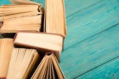 Alte und benutzte Bücher oder Lehrbücher des gebundenen Buches auf blauem hölzernem Schreibtisch Stockfoto