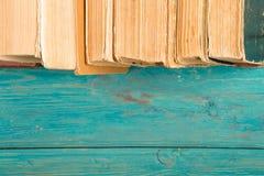 Alte und benutzte Bücher oder Lehrbücher des gebundenen Buches auf blauem hölzernem Schreibtisch Lizenzfreies Stockbild