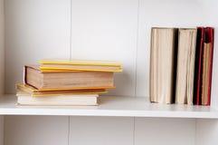 Alte und benutzte Bücher oder Lehrbücher des gebundenen Buches auf hölzernem Bücherregal Lizenzfreie Stockbilder