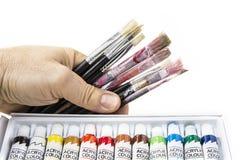Alte und benutzte Bürsten in der Hand mit Acrylfarbe auf weißem Hintergrund Lizenzfreie Stockfotos