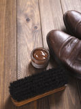 Alte und benutzte Schuhe zusammen mit Reinigungsprodukten auf braunem Holztisch mit Stockfotos