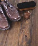 Alte und benutzte Schuhe zusammen mit Reinigungsprodukten auf braunem Holztisch mit Lizenzfreie Stockfotografie