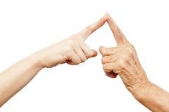 Alte und junge Hand, die in der Note ist Stockfotos