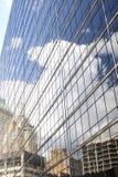 Alte und moderne Gebäude und ein sehr blauer Himmel mit sehr hohen weißen flaumigen Wolken werden in der Seite eines hohen Glasge stockfoto