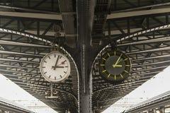 Alte und neue Uhr neben einander auf der Plattform der Bahnstation Lizenzfreie Stockbilder