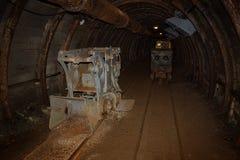Alte und rostige Bergwerkmaschine und -zug mit Lastwagen im Minenschacht mit hölzernem Zimmern stockbild