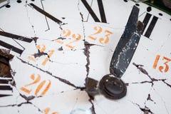 Alte und schädigende Uhr mit den römischen Ziffern, eine Minute zum Mitternacht markierend Stockbild