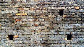 Alte und schmutzige Backsteinmauer mit drei Löchern Stockfotografie