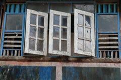 Alte und verblaßte hölzerne blaue und weiße Fenster, traditionelle Fassade des thailändischen Hauses mit offenem Fenster Stockfotografie