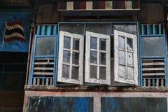 Alte und verblaßte hölzerne blaue und weiße Fenster, traditionelle Fassade des thailändischen Hauses mit offenem Fenster Lizenzfreies Stockbild