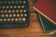 Alte und Weinleseart Verfassermaschine und Stapel von Büchern auf Holztisch - im Weinleseton Stockbild