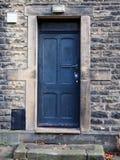Alte verblaßte blaue Tür mit Steintürrahmen Stockfoto