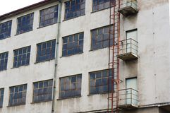 Alte verfallende Fabrik außen mit rostiger Leiter Stockfotos