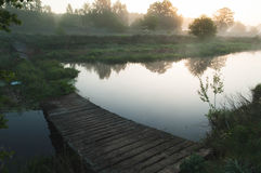 Alte verfallene Brücke über einem Fluss an der Dämmerung, Lizenzfreies Stockfoto