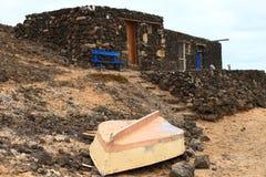 Alte verfallene Häuser und umgeworfenes Fischerboot auf der spanischen Insel von Les Lobos Stockfotografie