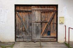 Alte verfallene hölzerne Garagentoren mit Briefkasten brachten an der rechten Seitenwand an Stockfotografie