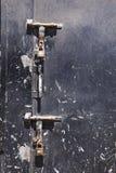 Alte verkratzte schwarze Stahltür mit zwei großen rostigen Klinken und Vorhängeschlössern, die von ihnen hängen Stockfoto