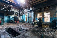 Alte verlassene Fabrik mit rostigen Überresten von industriellen Werkzeugmaschinen in der Werkstatt lizenzfreie stockbilder