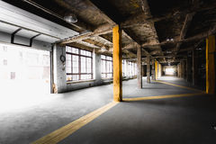 Alte verlassene Fabrikhalle mit großen Fenstern Stockfotos