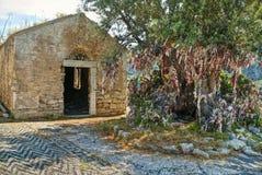 Alte verlassene Kirche mit großem Olivenbaum und bunten Lappen Lizenzfreie Stockfotos