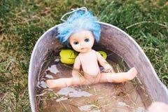 Alte verlassene Puppe in einem Becken des Wassers Lizenzfreie Stockbilder