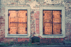 Alte verlassene rustikale Backsteinmauer mit geschlossenen hölzernen Fenstern Hintergrund für Fotografen oder Designer Lizenzfreies Stockfoto
